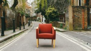 a red armchair sitting in the middle of a street